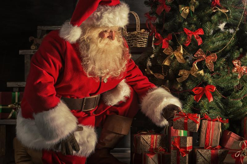 Santa+Claus+brought+gifts+for+Christmas.+Santa+is+placing+gift+boxes+under+Christmas+tree