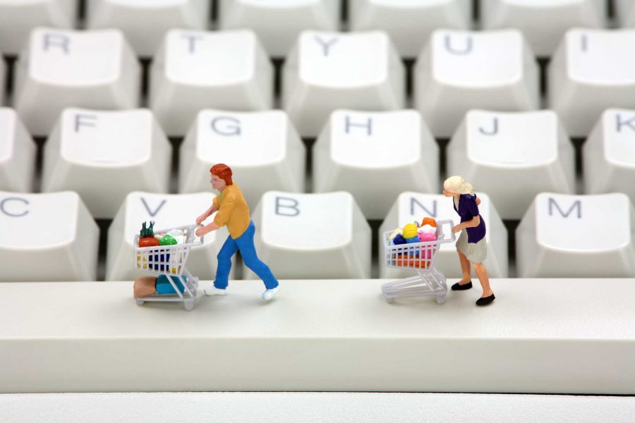 Miniature+shoppers+with+shopping+carts+on+a+computer+keyboard.+Online+shopping+concept.