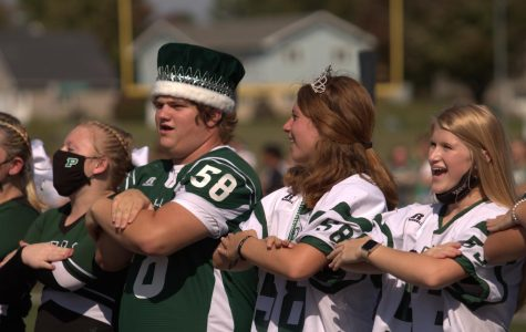 Homecoming King Cole DeWaard and Queen Annika Boonstra cheer along with the cheerleaders.