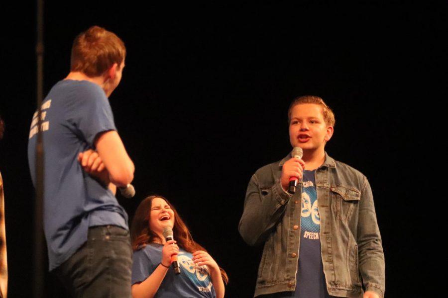 Senior Travis Mitchell and senior Will Rassmussen preforms while junior Maggie Leach laughs behind them.