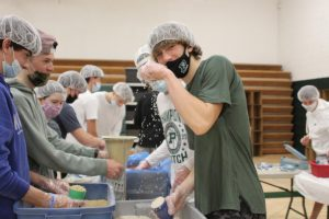Junior Isaac Semini poses with rice while also packaging meals.